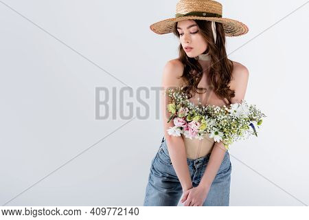 Young Woman In Straw Hat, Jeans And Flowers In Blouse Isolated On Grey.