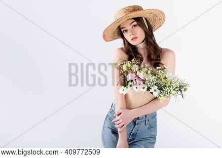 Woman With Flowers In Blouse Posing In Straw Hat Isolated On Grey.