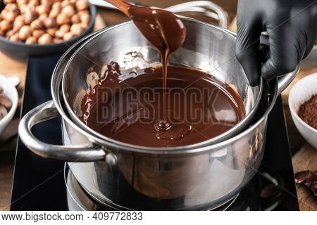 Confectioner prepares the melted dark chocolate in a bowl on a wooden table. Liquid hot chocolate. Confectionery. Cooking melted chocolate