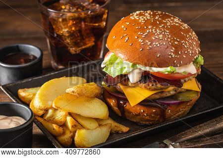 Grilled hamburger with double cutlet, fries in a metal bowl and cola on a wooden table. Hamburger and French fries. Fast food concept.