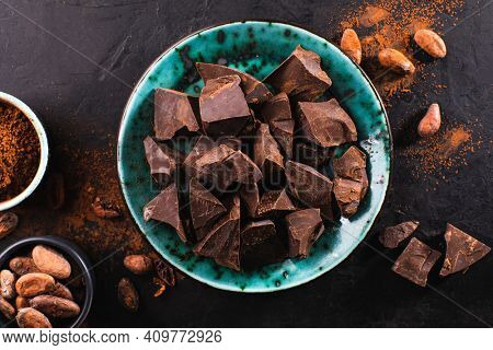 Pieces of dark chocolate in a vintage bowl, cocoa powder and cocoa beans on a dark textured background, top view. Confectionery chocolate background. Chunks of chocolate.