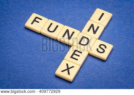 index funds - crossword in ivory letter tiles against textured handmade paper, stock market and investing concept