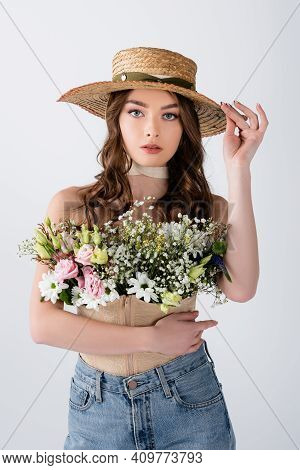 Brunette Model Holding Sun Hat And Flowers In Blouse Isolated On Grey.