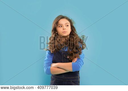 Awesome Beauty. Adorable Baby Girl Keeping Arms Crossed On Blue Background. Brunette Girl With Long