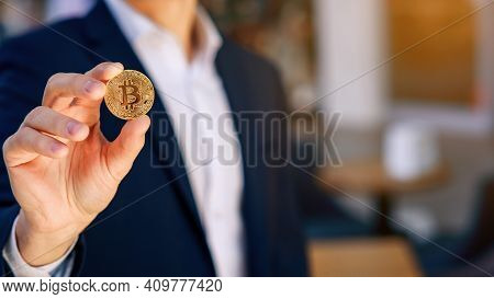 Successful Businessman Holds A Gold Bitcoin Coin In His Hand. Cryptocurrency Business Concept. Elect