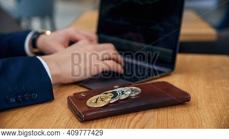 Businessman Works On A Laptop In His Workplace. Cryptocurrency Business Concept. Electronic Virtual