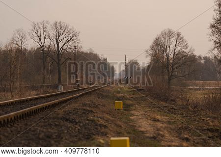 A Railroad Track, A Single, Straight Track Across Flat Terrain. There Are Trees And Tall Grass On Bo