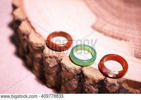 Rings Made Of Colored Semi-precious Stones On Tree Bark