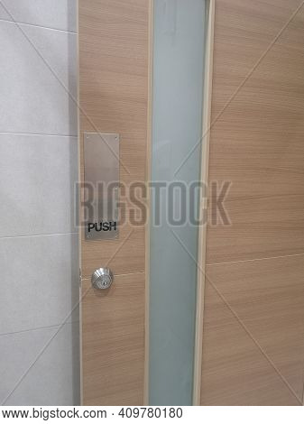 Push Type Door Handle, Black Text Latch In The Stainless Steel Plate And Keyhole On Wooden Door