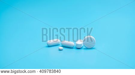 Round White Tablets Pills On Blue Background. Tablets And Caplets Pills Pharmaceutical Dosage Form.