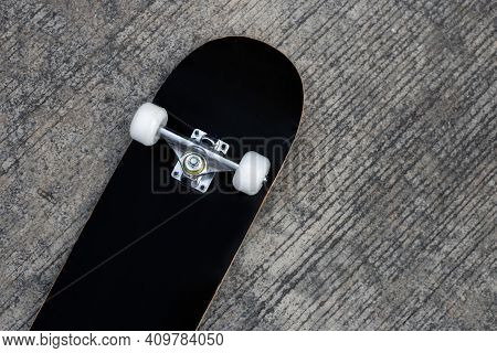 Black Skateboard On Cement Ground. Top View