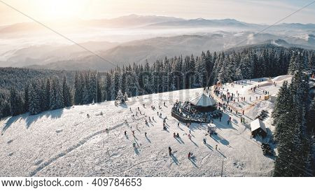 Winter snow resort at sun mountain aerial. People at nature landscape. Ski slope for active sport. Snowy pine trees forest. Tourist attraction at Carpathian mounts ridge, Bukovel, Ukraine, Europe