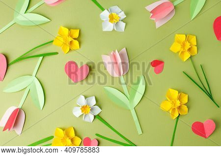 Pink Origami Tulips And Yellow Origami Narcissus On Green Pastel Background. Top View. Paper Cut Art