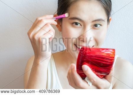 Portrait Of Happiness Asian Woman Applying Concealer On Her Facial Skin With Brush. Concealer Is A T