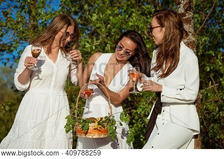 Three Cheerful Girlfriends In A White Dress In Nature With A Glass Of Wine On The Background Of Tree