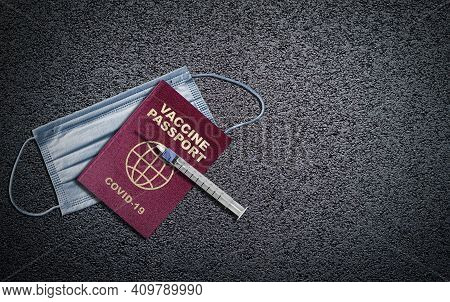 Covid-19 Vaccine Passport Concept With Syringe Needle On Passport And Face Mask On Asphalt Backgroun