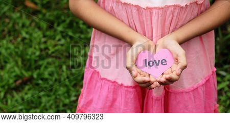 :ove Concept - Young Hand Hold Love Card Against Nature Background With Space
