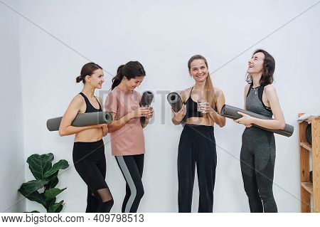 Laughing Friendly Women Socialising At Yoga Club, Holding Rolled Mats Under Arm