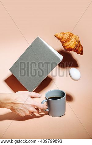 Male Hand Picking Coffee Mug From Peach Surface. Other Items Hovering In Air