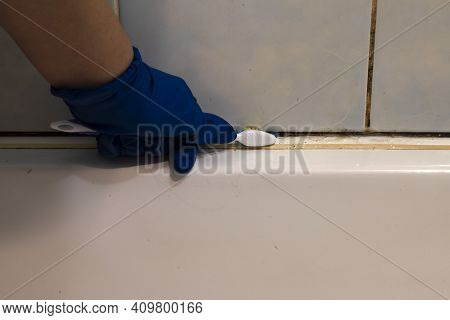A Hand In A Blue Glove Cleans The Dirty Joints Between The Tiles And The Bathroom With An Old Toothb