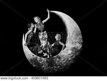 Fashion Night Dress. Group Of Beautiful Young Women Posing On Crescent Moon In Long Evening Elegant