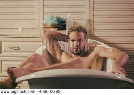 Gay Relax Naked In Bathtub In Bathroom. Man With Muscular Legs, Chest In Bath. Hygiene Morning Routi