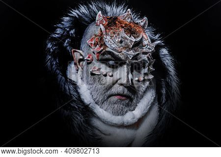 Dark Arts Concept. Devil Man With White Beard Dressed Like Monster. Evil On Black Background, Close