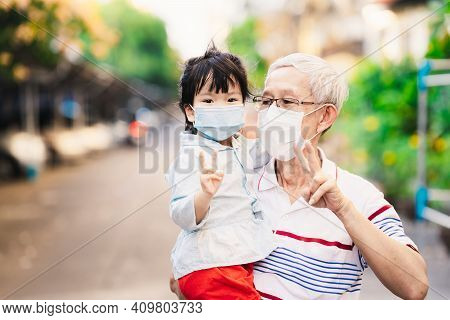Family Wearing Medical Face Mask And Raised Two Fingers. Grandfather Carried Granddaughter Wearing S