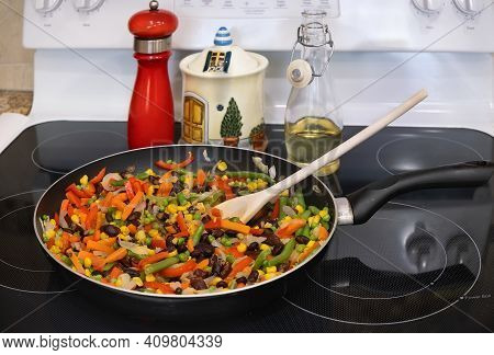 Frying Pan With Vegetable Mix On The Stove Top.  Cooking Vegan Meal.