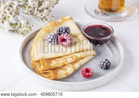 Crepes With Berries And Red Sauce On A Plate. Thin Pancakes With Ice  Fresh Berries.