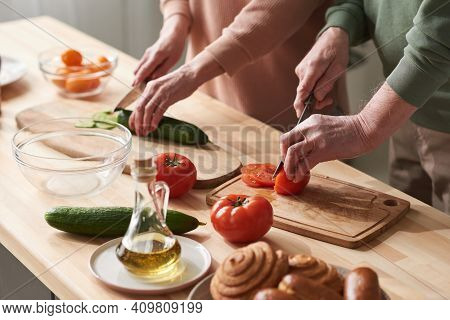 Close-up Of Couple Cutting Fresh Vegetables On Cutting Board And Preparing Vegetable Salad