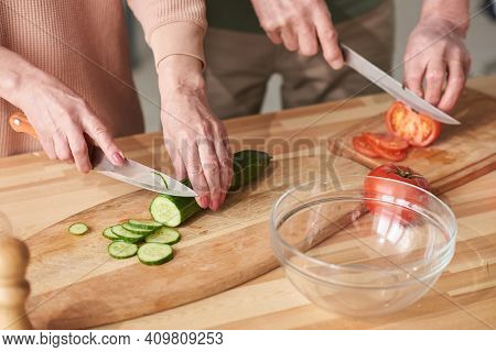Close-up Of Couple Cutting Fresh Cucumber And Tomato On Cutting Board For Salad