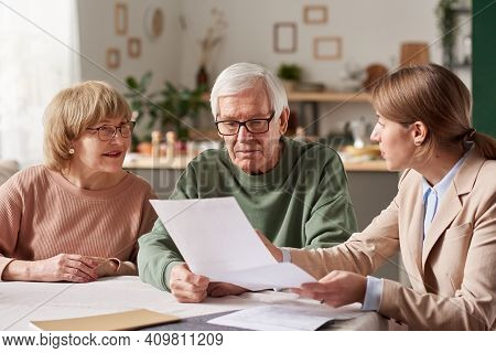Senior Couple Sitting At The Table And Discussing Documents With Real Estate Agent They Making A Wil