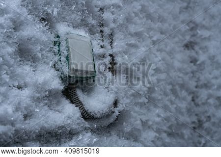 Snow Covered Device With Switch On Frozen Wall In Winter