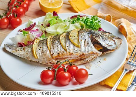 Tasty Grilled Dorado Fish With Lemons And Herbs Served On The Plate With Tomatoes And Salad
