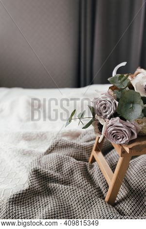 Romantic Morning. Wooden Coffee Table With Flowers On Bed With Blanket. Lilac Roses With Eucalyptus