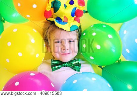 Cute Smiling Child Clown With Multicolored Balloons. Birthday Party Concept. April Fools Day Celebra