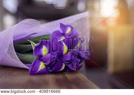 A Beautiful And Delicate Bouquet Of Irises Flowers In An Interesting Package Lie On A Wood Table In
