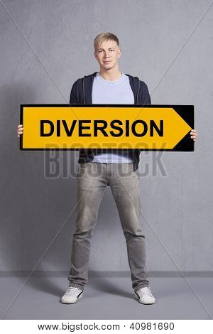 Friendly man holding diversion sign isolated on grey background.