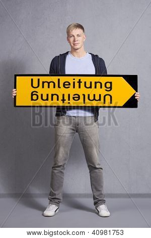 Friendly man holding diversion sign Umleitung isolated on grey background. German version.