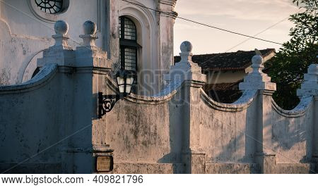 Old Colonial Church Building And Outside White Walls With A Street Lamp In Focus As Evening Light Br