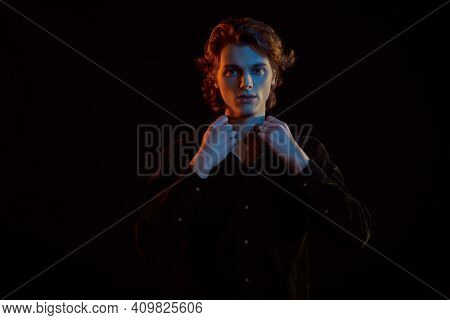 Portrait of a handsome young man with wavy blond hair looking at the camera in dark. Black background with copy space. Men's beauty.