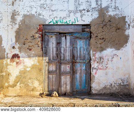 Closed Wooden Weathered Door And Shabby Old Grunge Stone Wall On Abandoned District. Arabic Text Abo