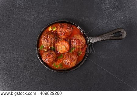 Stewed Meatballs In Tomato Sauce In A Pan On A Dark Background.