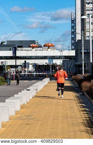 Madrid, Spain - February 7, 2021: Runner Running On Pedestrian Walkway In Cuatro Torres Financial Di