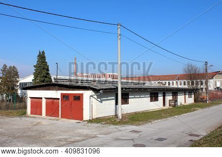 Elongated White Garage And Storage Building In Old Industrial Part Of Town Surrounded With Cracked P