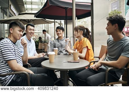 Young Asian Adults Men And Woman Sitting Chatting Relaxing In Outdoor Coffee Shop