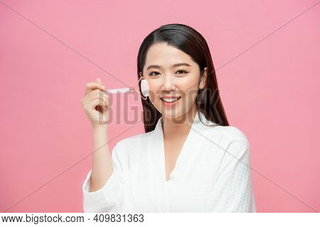 Beautiful Young Woman With Perfect Skin Using A Rose Quartz Face Roller With Natural Quartz Stones