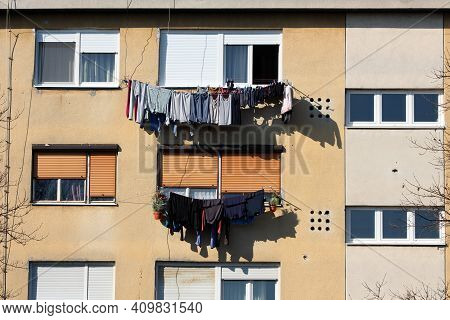 Freshly Washed Laundry Left To Dry On Warm Winter Sun On Edge Of Apartment Windows Of Old Apartment