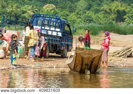 Luang Prabang  Laos - April 2012: Local people  on the Nam Khan river in a lush tropical landscape